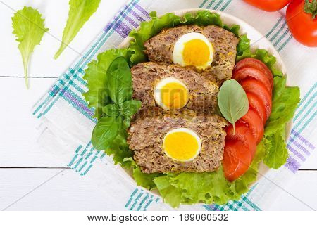 Meatloaf stuffed boiled egg with fresh tomato and lettuce leaves on a plate on a white wooden table. Top view. Close-up.