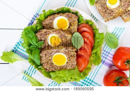 Meatloaf stuffed boiled egg with fresh tomato and lettuce leaves on a plate on a white wooden table.