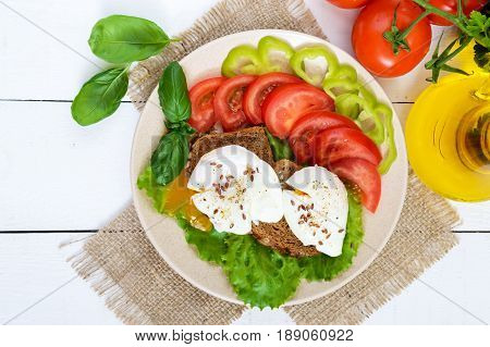 Sandwich with egg poached lettuce black bread with seeds tomatoes sweet pepper on a plate on a white wooden table. The top view