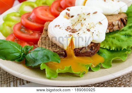 Sandwich with egg poached lettuce black bread with seeds tomatoes sweet pepper on a plate on a white wooden table. Close up