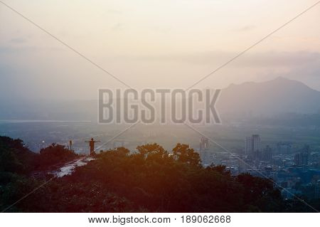 silhouette of man spreading arms out with city and mountain in the background in sunset with big copy space