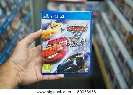 Bratislava, Slovakia, June 1, 2017: Man holding Cars 3 Driven to Win videogame on Sony Playstation 4 console in store