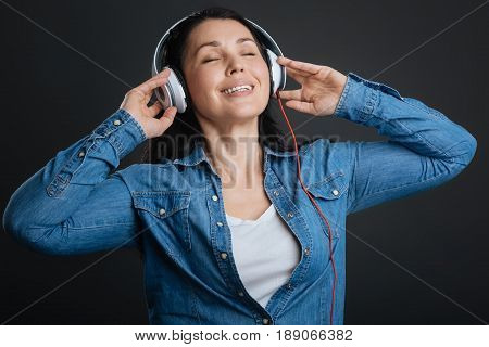 Musical ecstasy. Emotional dreamy graceful lady enjoying a prefect playlist while having the headphones on and standing isolated on grey background