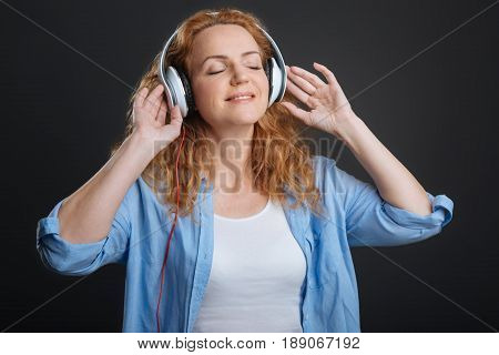 Amazing feelings. Charming bright dreamy woman spending her free time enjoying her hobby while having headphones on and listening to music