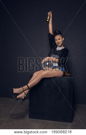 Glamour Asian Disco Girl With Golden Bottle And Disco Ball Smiling And Looking At Camera