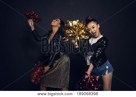 Carefree Stylish Young Women Having Fun With Pom-poms Isolated On Black