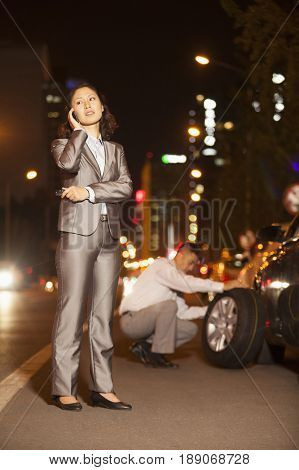 Chinese woman with boyfriend changing car tire