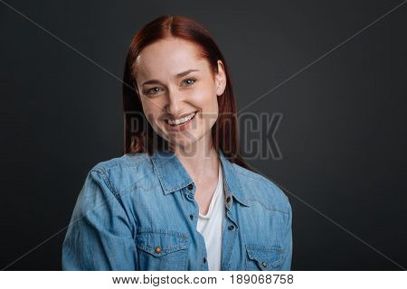 Fresh and bright. Smiling pleasant red haired woman posing for a photographer and smiling while standing isolated on grey background