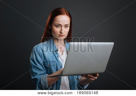 Committed employee. Smart charismatic bright woman employing the laptop while working from home and perusing a report