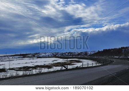 the highway with an asphalt coat against the background of the blue sky with white clouds