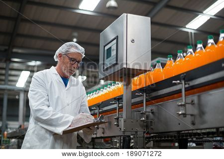 Factory engineer maintaining record on clipboard in drinks production plant