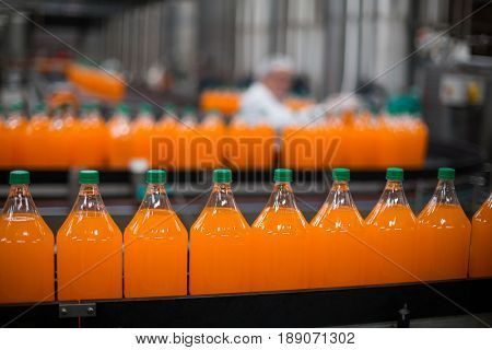 Bottle of juice processing on production line in bottle factory