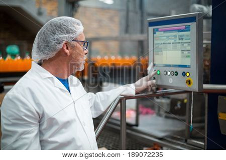 Factory engineer operating machine in drinks production plant