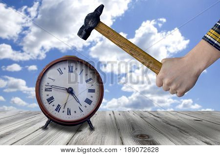 Man hand holding old hammer smashing  clock