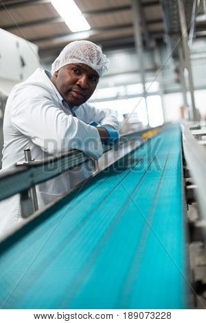 Factory engineer leaning on production line in drinks production plant