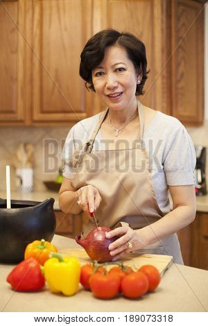 Older Asian woman chopping onion in kitchen