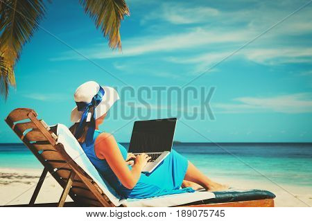 remote work cocept -young woman with laptop on tropical beach