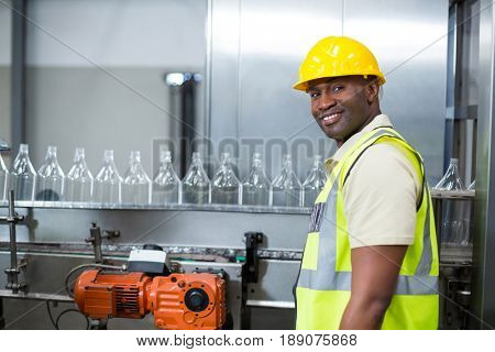 Smiling factory worker standing next to production line at drinks production plant
