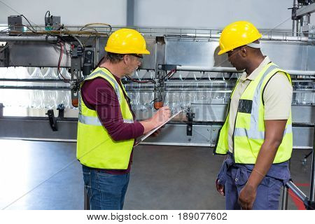 Two factory workers with clipboard working next to production line in drinks production plant
