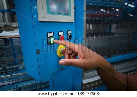 Hands of factory worker pressing a green button on the control board in factory