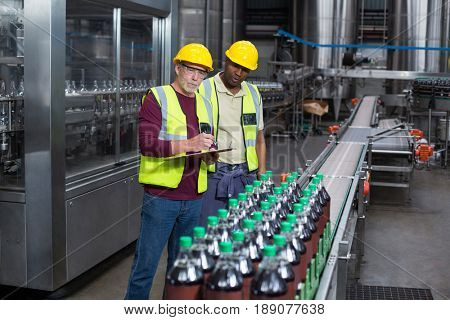 Two factory workers monitoring cold drink bottles at drinks production plant