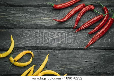 Frame of a red and yellow chili pepper of black wooden table. Rustic cuisine. Hot pepper of red and yellow color. Overhead view at red and yellow chili pepper.