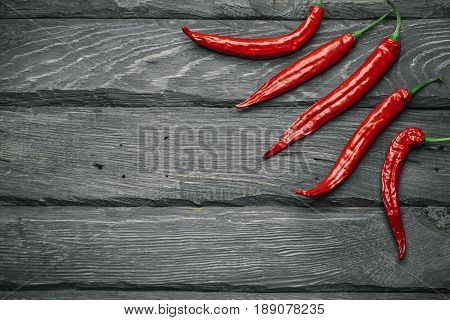 Frame of a red chili pepper of black wooden table. Rustic cuisine. Hot pepper of red color. Overhead view at red chili pepper.