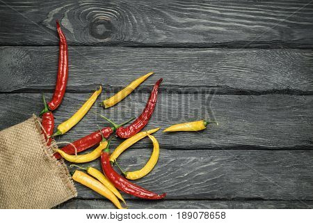 Red and yellow chili pepper of black wooden table in the bagging. Bagging with chili pepper. Overhead view at chili pepper on a wooden table. Place for text.
