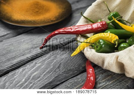 Red yellow and green chili pepper of black wooden table. Bagging with chili pepper. Green pepper in the bagging. Black plate with powdered pepper.