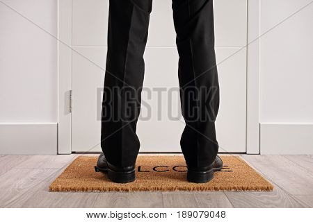 Person standing on a doormat with the word welcome written on it in front of a closed door