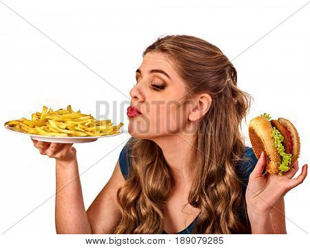 Woman eating french fries and hamburger. Portrait of student consume fast food on table. Girl trying to eat junk. Girl is having supper after hard day's work. Good appetite and metabolism