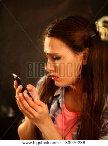 Woman crying by phone. Girl talking on phone . Portrait of sad female behind window with raindrops. Rain black background.