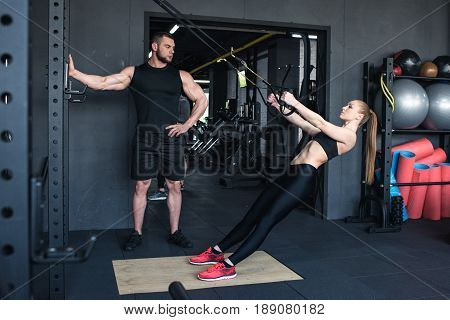 Sportswoman Training With Trx Resistance Band While Trainer Looking At Her In Sports Center