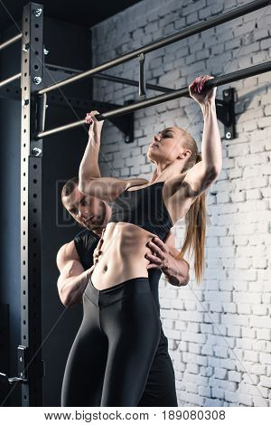 Sportswoman Doing Pull Up While Trainer Helping Her In Sports Center