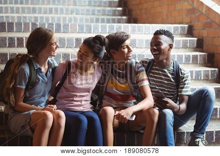Happy classmates sitting on staircase at school