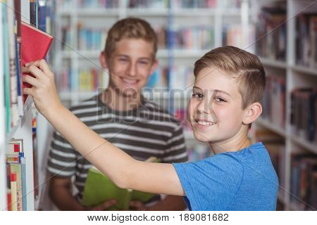 Schoolboys selecting book in library at school