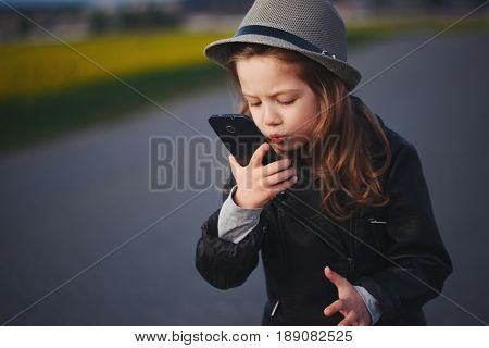 photo of little funny girl with smartphone