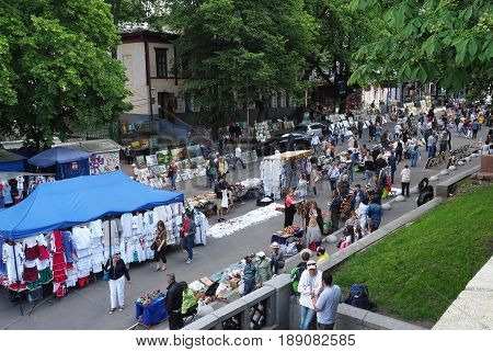 KIEV - UKRAINE - MAY, 2017: Fair on Vladimirskaya street on the Day of Kiev. People walk around the tents with Ukrainian souvenirs. Street lined with paving stones, chestnuts - a symbol of Kiev