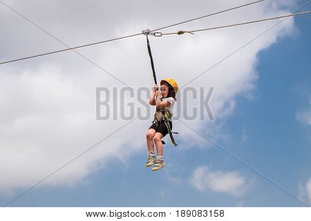 Little Girl With Safety Equipment Enjoying Activities On Zipline