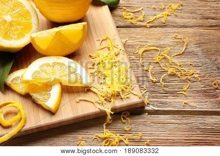 Board with cut lemons and zest on wooden table, closeup