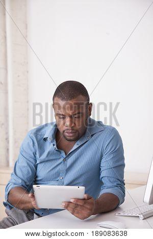 Black businessman using digital tablet at desk