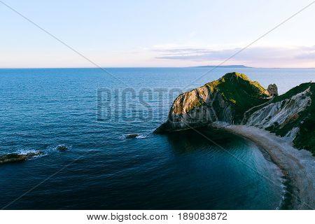 Bird's eye view over blue sea and Man O'War Beach, Dorset, Jurassic Coast, UK at sunset