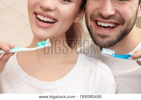 Young happy couple brushing teeth in bathroom