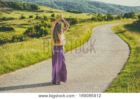 Woman with beautiful blonde hair meditating at the countryside.