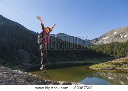 Caucasian hiker jumping for joy on boulder
