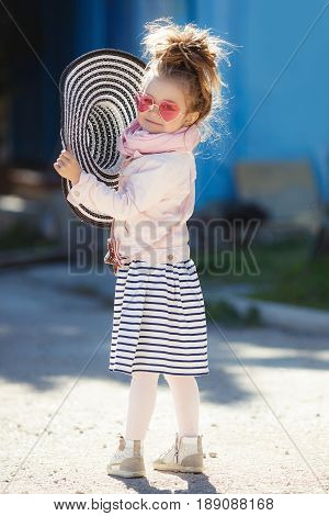 Beautiful little girl with blond hair, wearing glasses with pink glasses in the shape of hearts, striped hat with large fields, striped skirt, pink jacket, pink scarf, spending time alone outdoors in the afternoon, posing on blue background