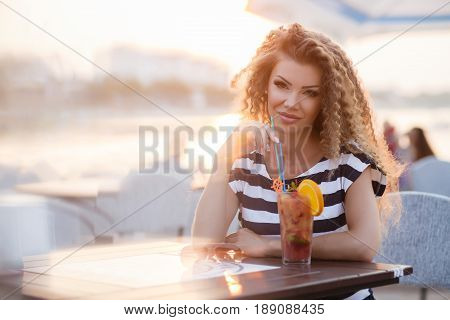 A beautiful, young woman,a brunette with long curly hair,dressed in a white light dress with dark blue stripes,a sweet smile and a tempting mole on the left side of her lips,big black eyelashes and professinal make-up,posing in the summer outdoors