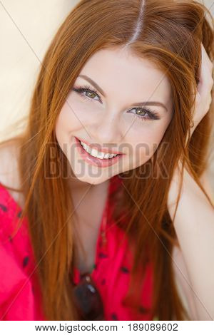 Young beautiful woman with long red, straight hair and green eyes, beautiful make-up, pink plump lips, sweet smile, spending time alone outdoors in the summer in the city, dressed in a red blouse, posing in the afternoon in the sunligh