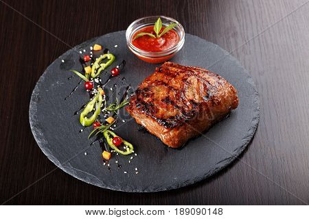 Steak on slate board. standing next to a gravy boat with ketchup. on the board is hot pepper diced carrots red currants sesame.