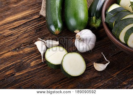 Raw zucchini slices and whole cooking vegetarian food space for text